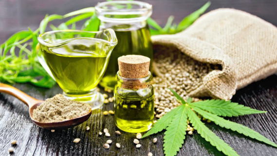 Hemp oil in two glass jars and sauceboat with grain in the bag, leaves and stalks of cannabis, a spoon with flour on the background of wooden boards (Hemp oil in two glass jars and sauceboat with grain in the bag, leaves and stalks of cannabis
